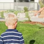 poika pelaa palloa pihanurmikolla